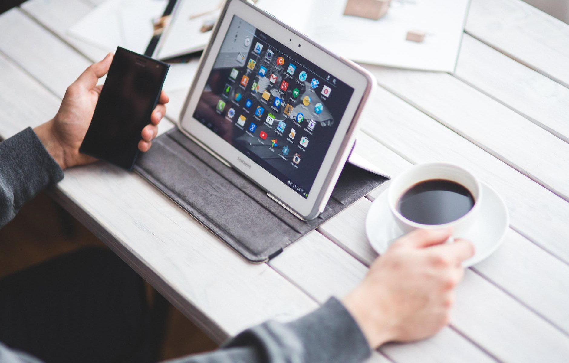 man drinking coffee and using digital tablet